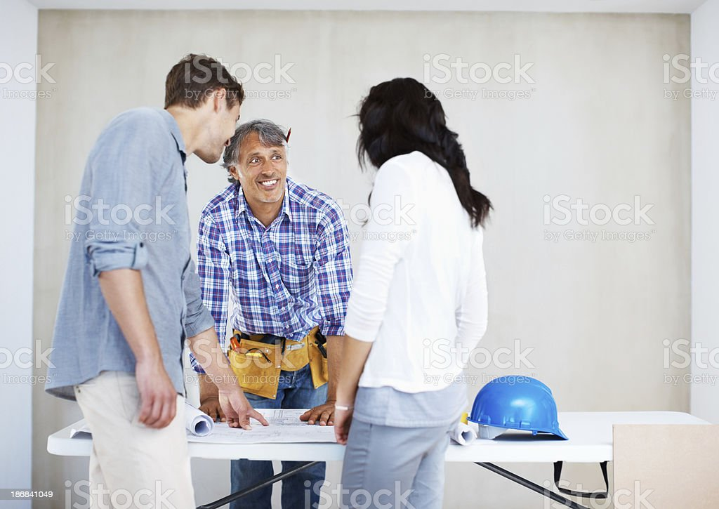 Couple discussing renovation plans with carpenter royalty-free stock photo