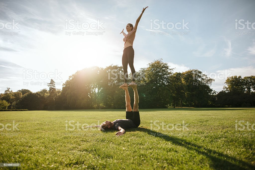Couple doing acrobatic yoga exercise at park stock photo