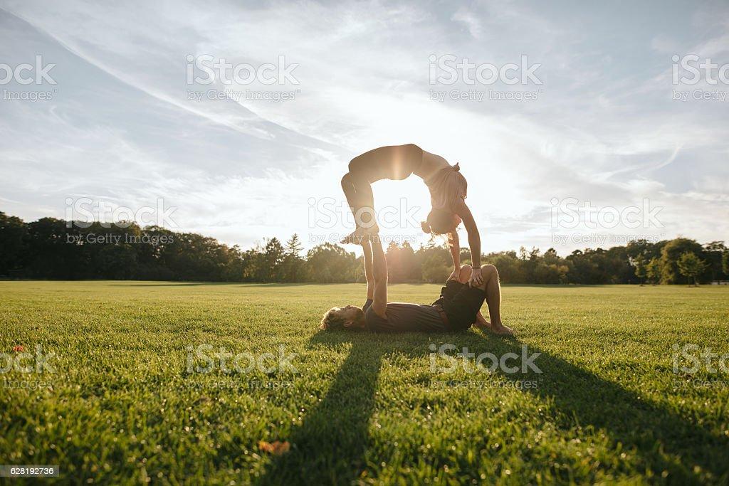 Couple doing acrobatic yoga exercise at park stock photo