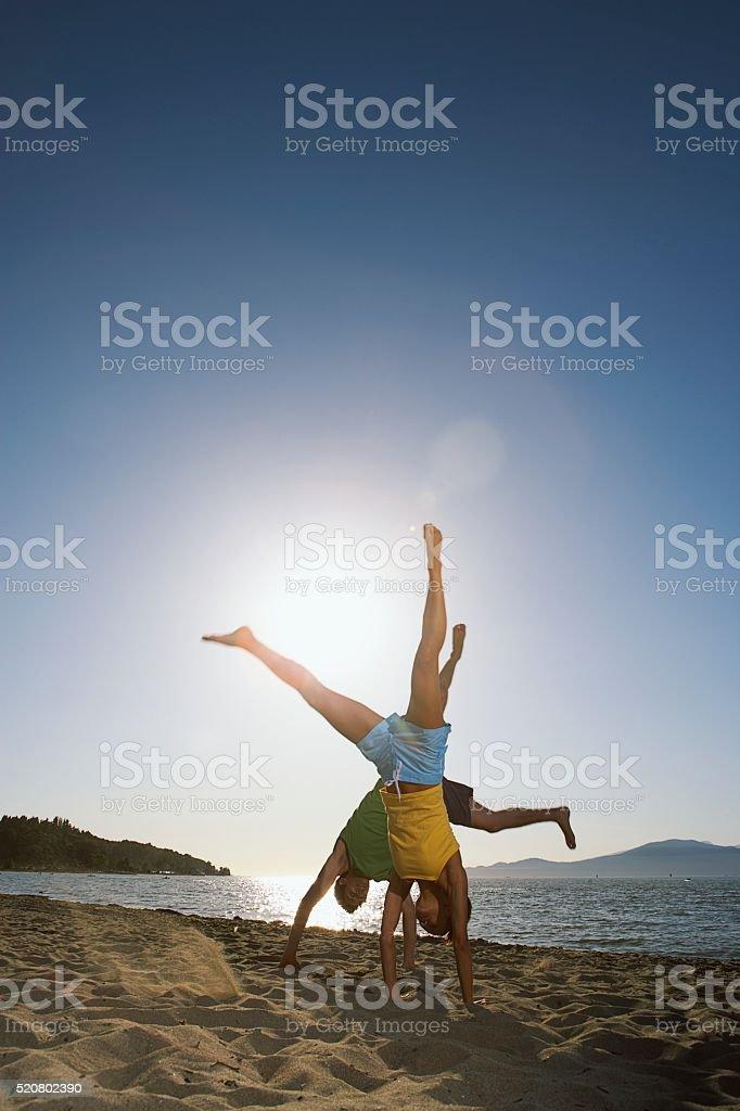 Couple doing cartwheels on the beach stock photo