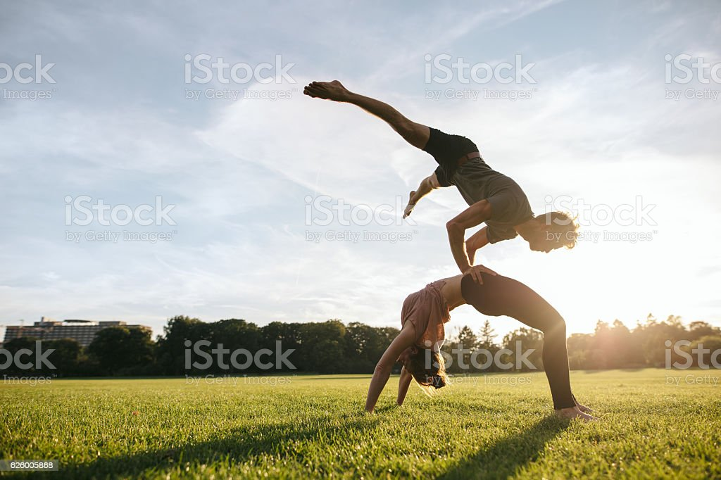 Couple doing pair yoga in park stock photo