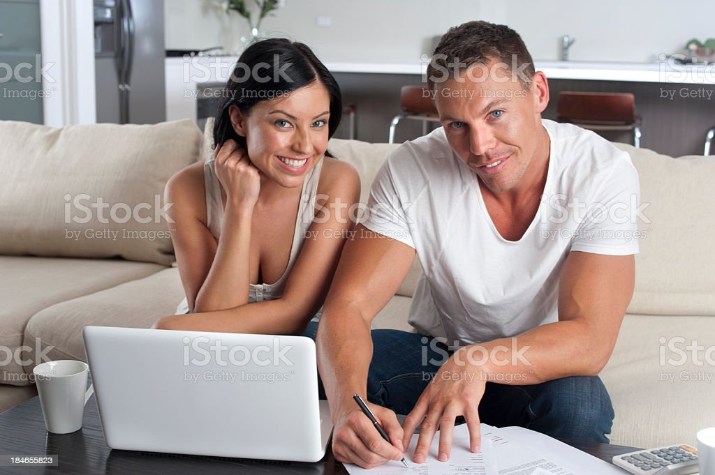 Couple doing paperwork with a laptop computer royalty-free stock photo