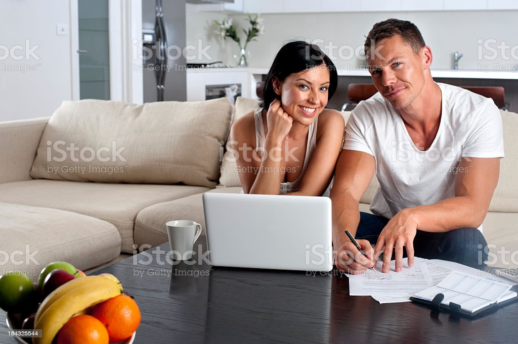 Couple doing paperwork with a laptop stock photo