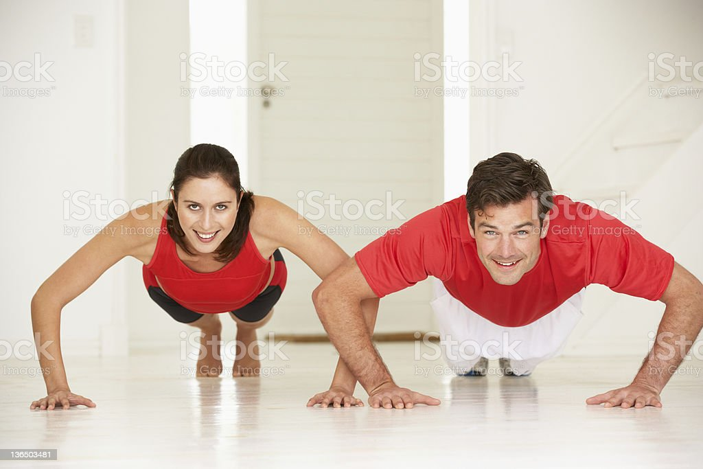 Couple doing push-ups in home gym royalty-free stock photo