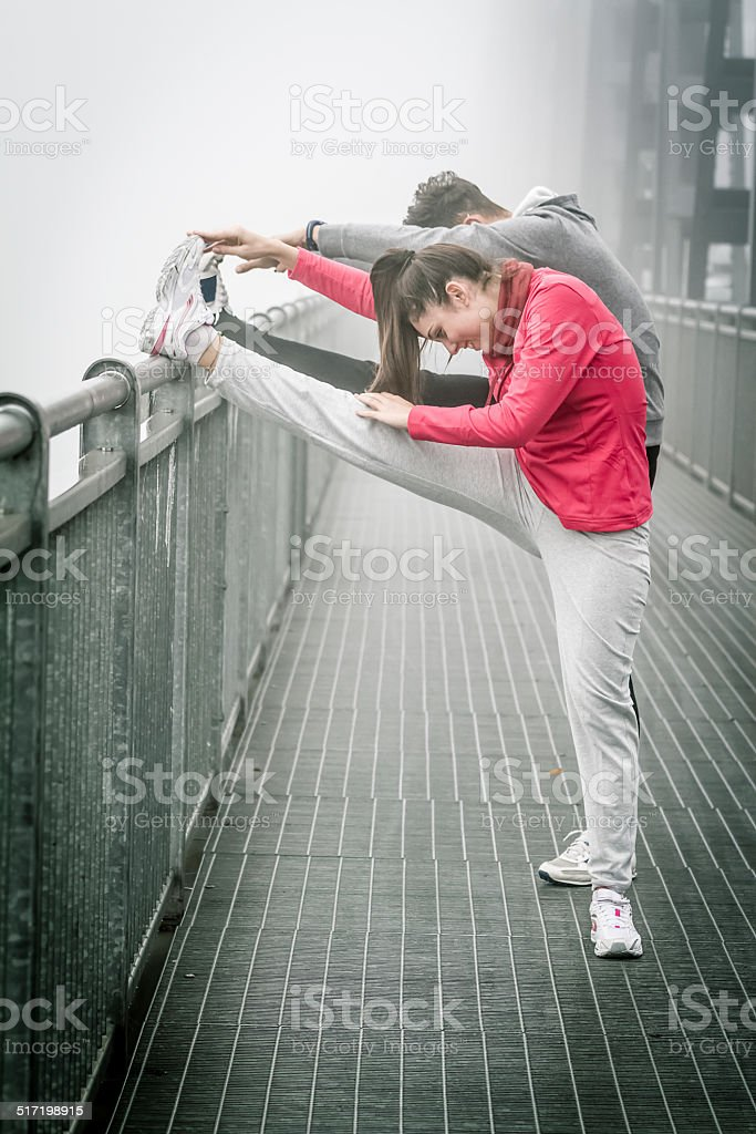Couple doing stratching in the fog on Iron Bridge stock photo