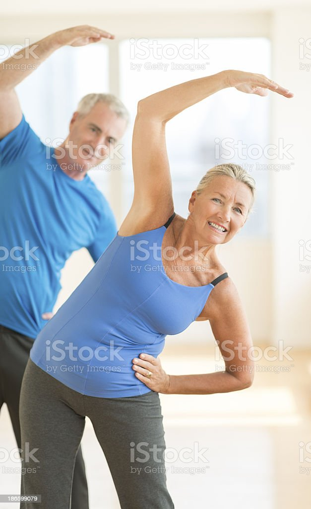 Couple Doing Stretching Exercise At Home royalty-free stock photo