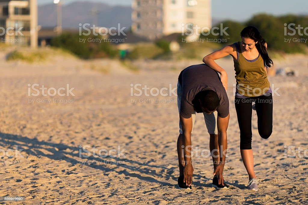 Couple doing stretching exercises at beach stock photo