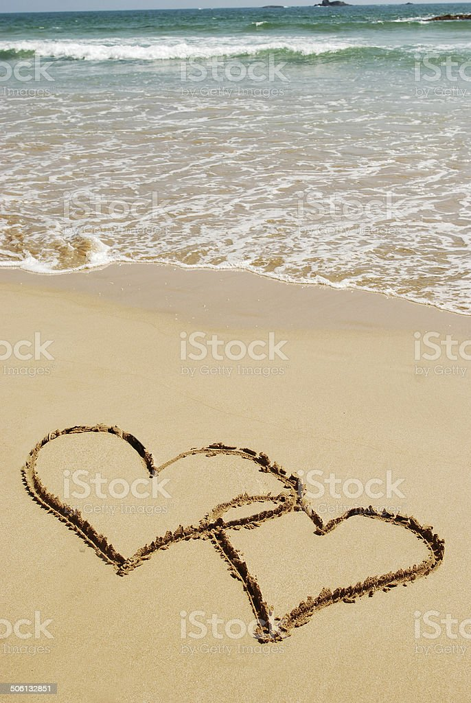 couple drawing a heart on wet golden beach sand stock photo