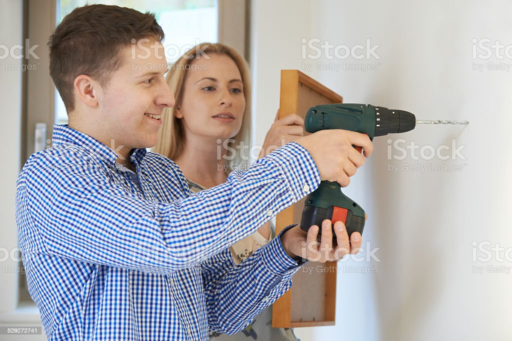 Couple Drilling Wall To Hang Picture Frame stock photo