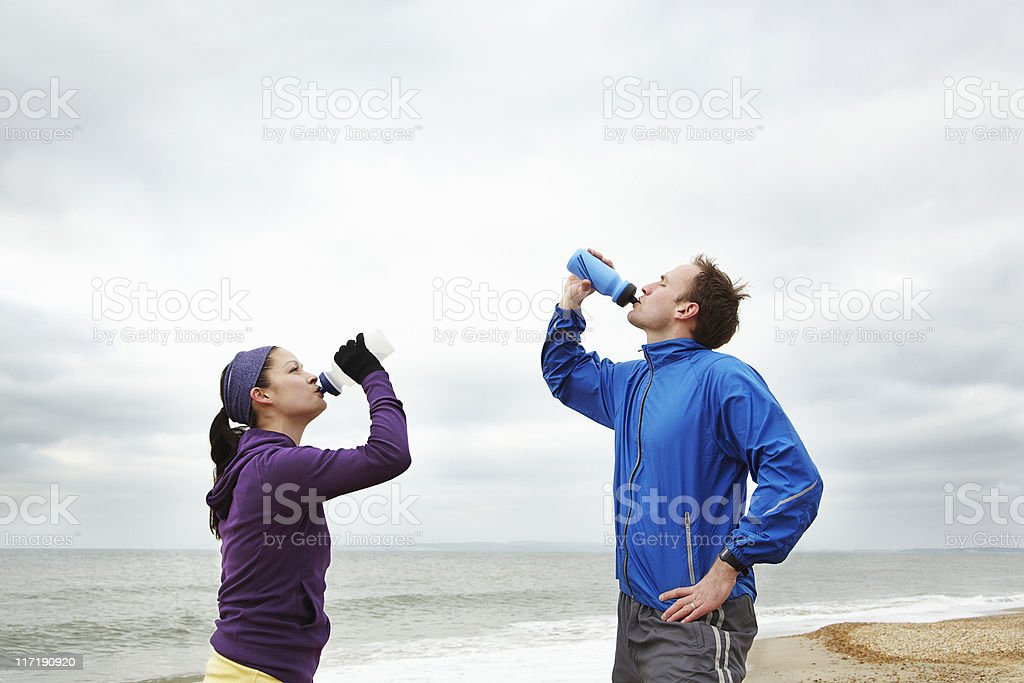 Couple drinking after exercise on beach stock photo