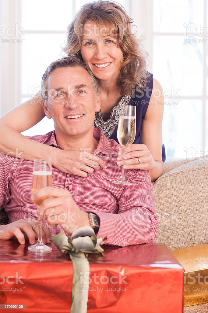 Couple drinking champagne near Christmas gifts royalty-free stock photo