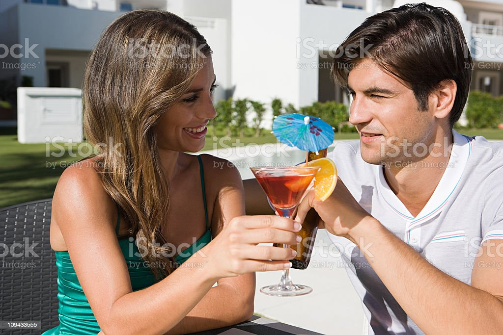 Couple drinking cocktail and beer on holiday stock photo