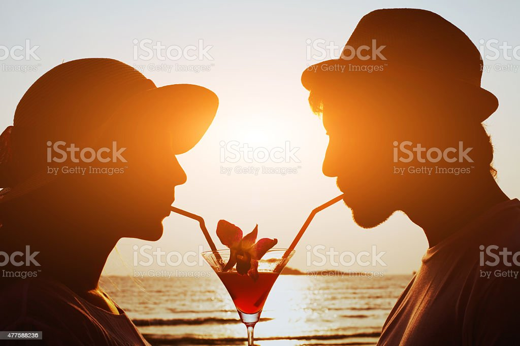 couple drinking cocktail together stock photo