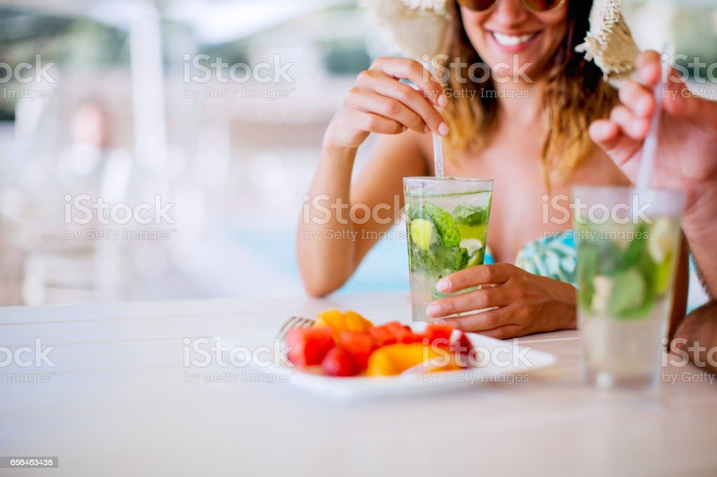 Couple drinking cocktails near pool stock photo