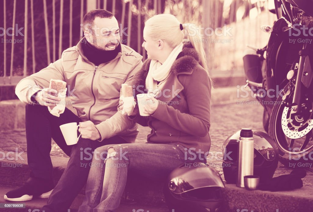 Couple drinking coffee near motorcycle stock photo