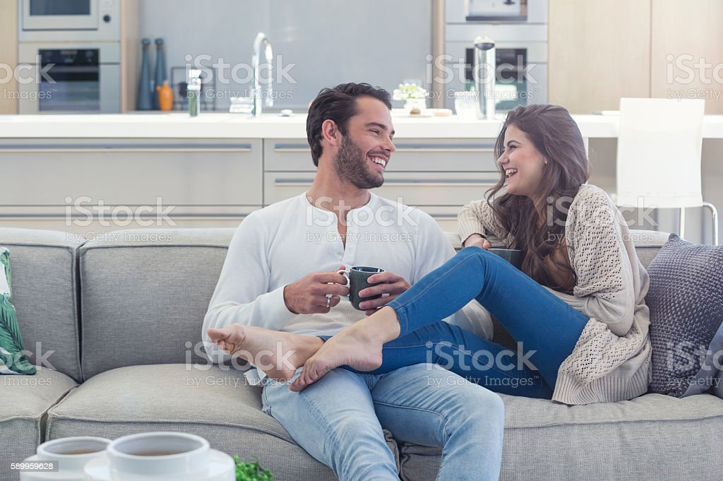 Couple drinking coffee on the sofa. stock photo