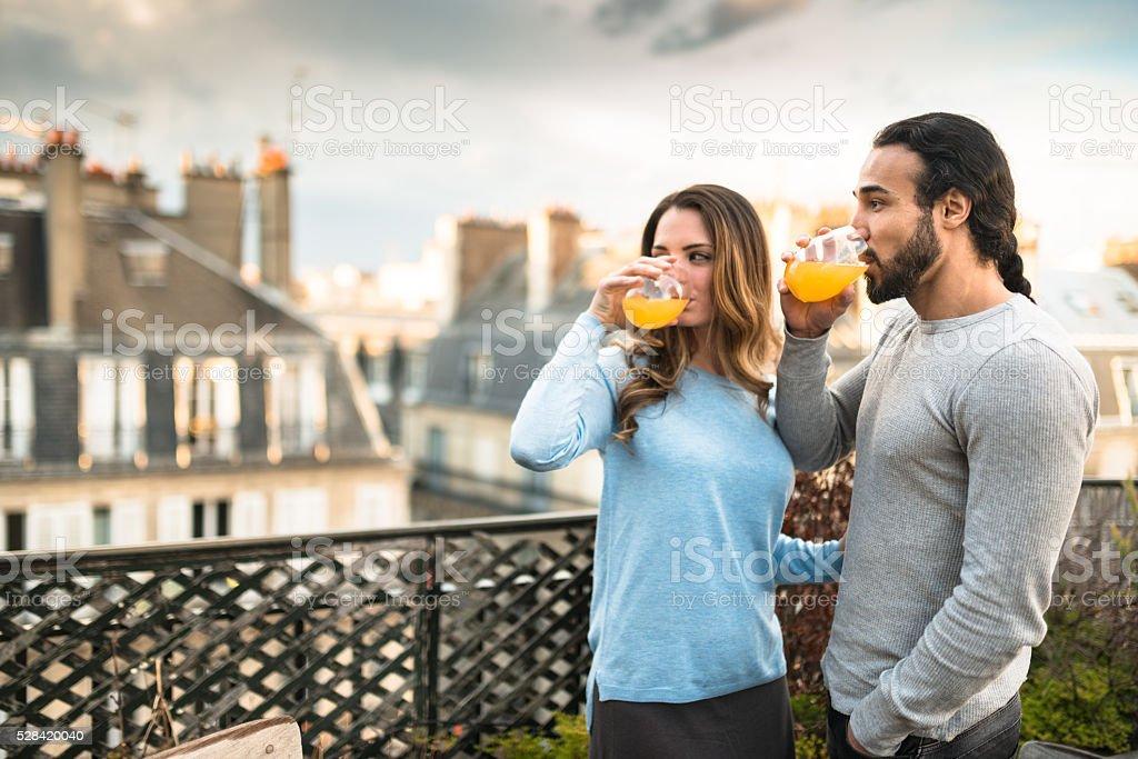 Couple drinking orange juice in the balcony stock photo