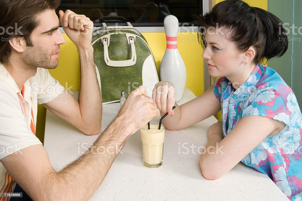 Couple drinking out of same glass royalty-free stock photo