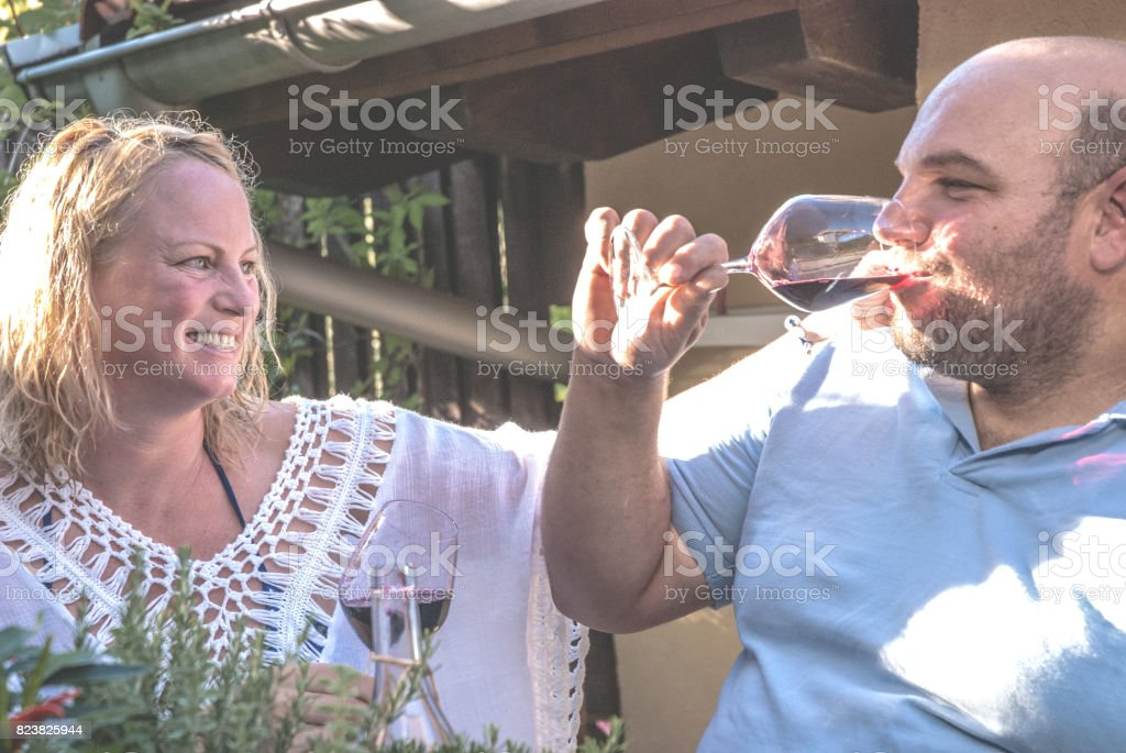 Couple Drinking Red Wine at Garden Party stock photo