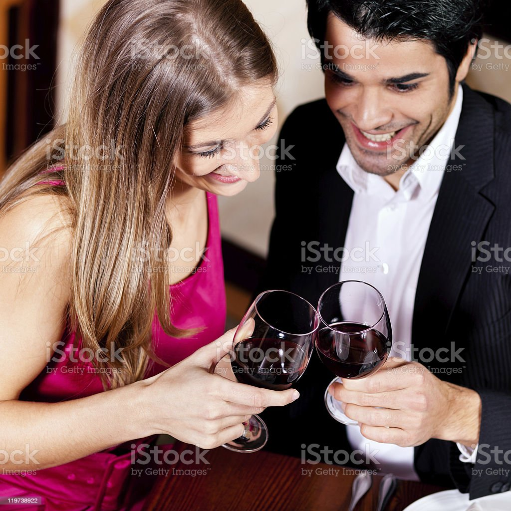 Couple drinking red wine clinking glasses royalty-free stock photo