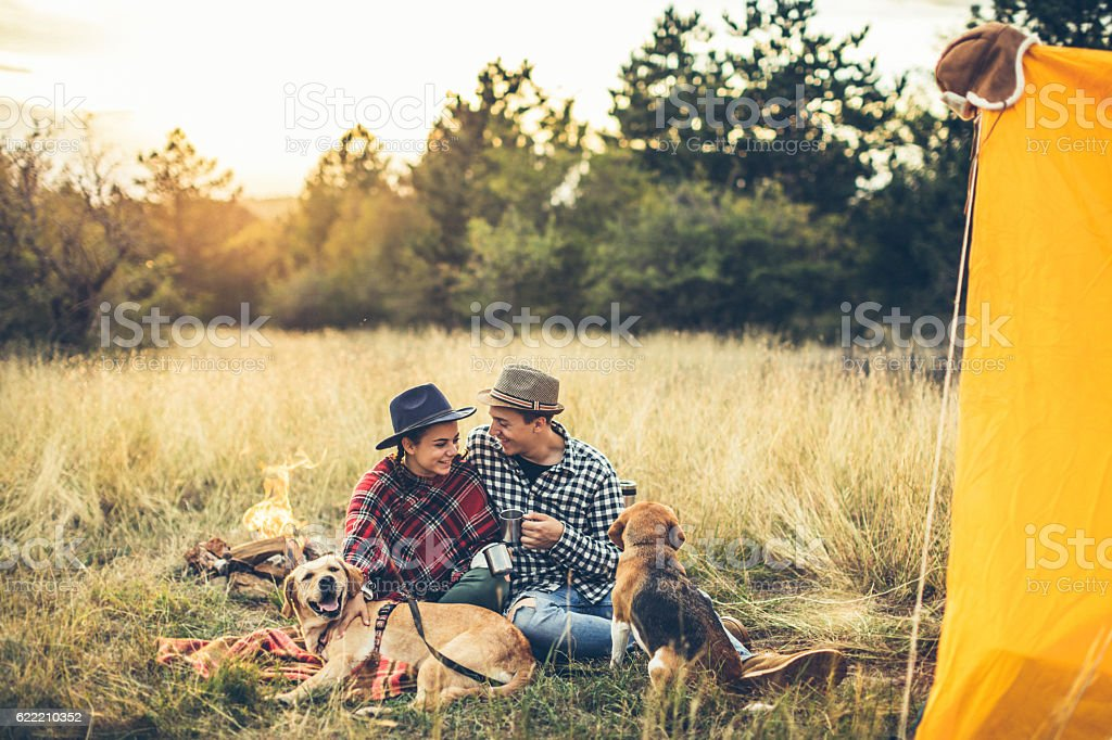 Couple drinking tea in front of bonfire stock photo