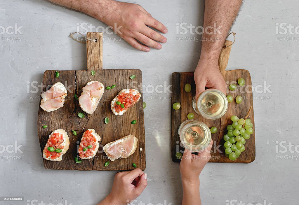 Couple drinking wine and eating appetizers for wine stock photo
