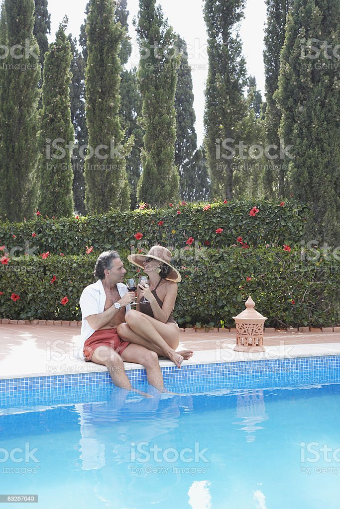 Couple drinking wine by pool royalty-free stock photo