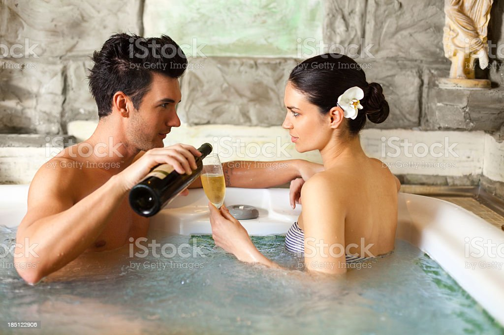 Couple drinking wine in jacuzzi royalty-free stock photo
