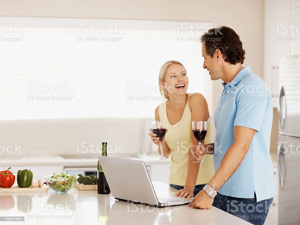 Couple drinking wine while using a laptop in the kitchen royalty-free stock photo