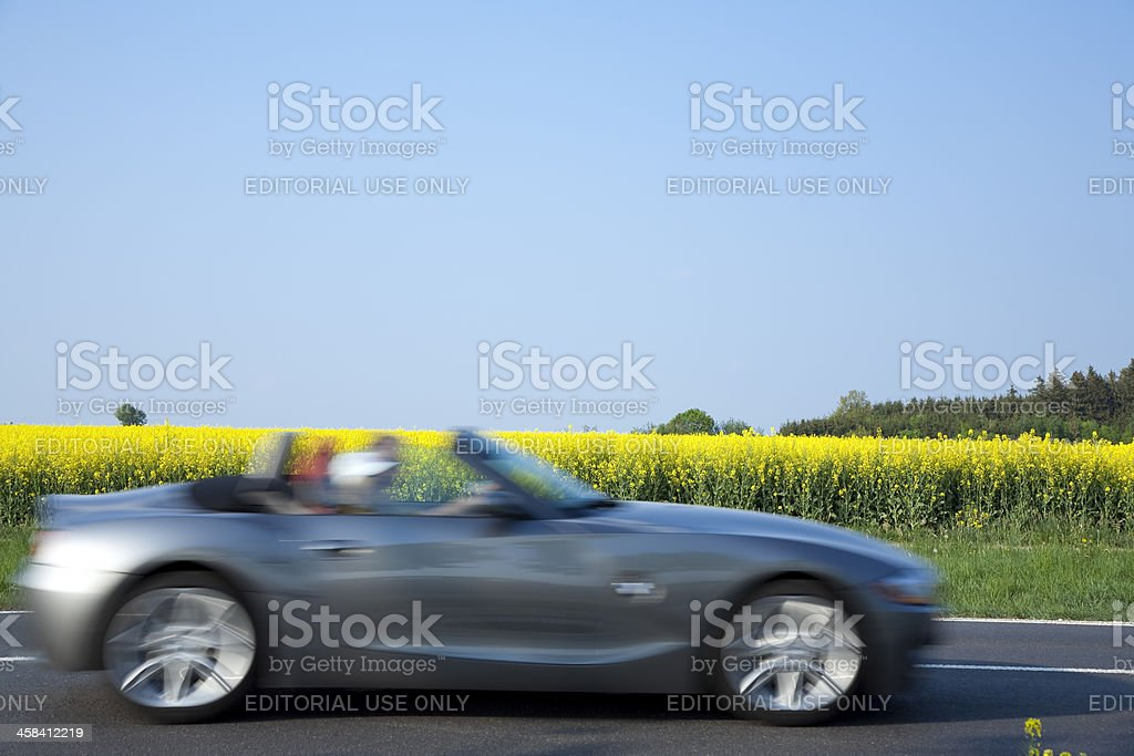 Couple drive BMW Z4 Roadster Convertible on rural road stock photo
