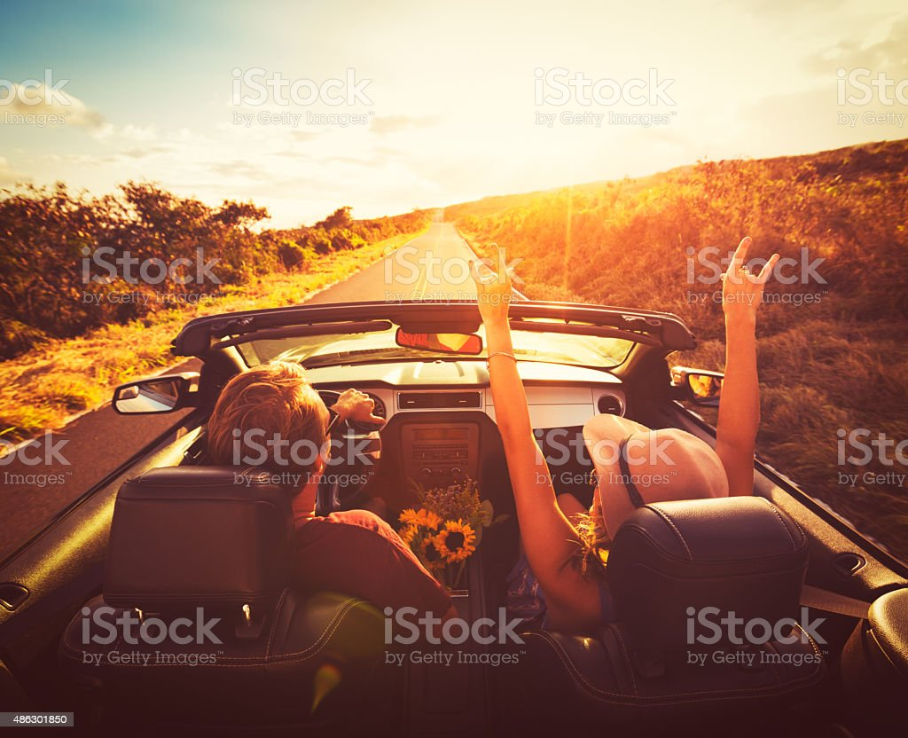 Couple Driving Convertable at Sunset stock photo