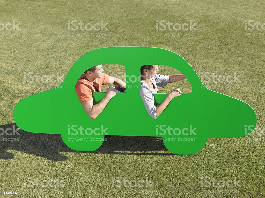 Couple driving in cutout car stock photo