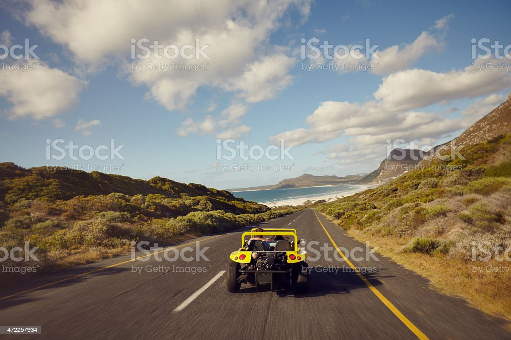 Couple driving in small car on open road stock photo