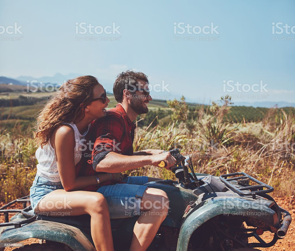 Couple driving off-road with quad bike stock photo