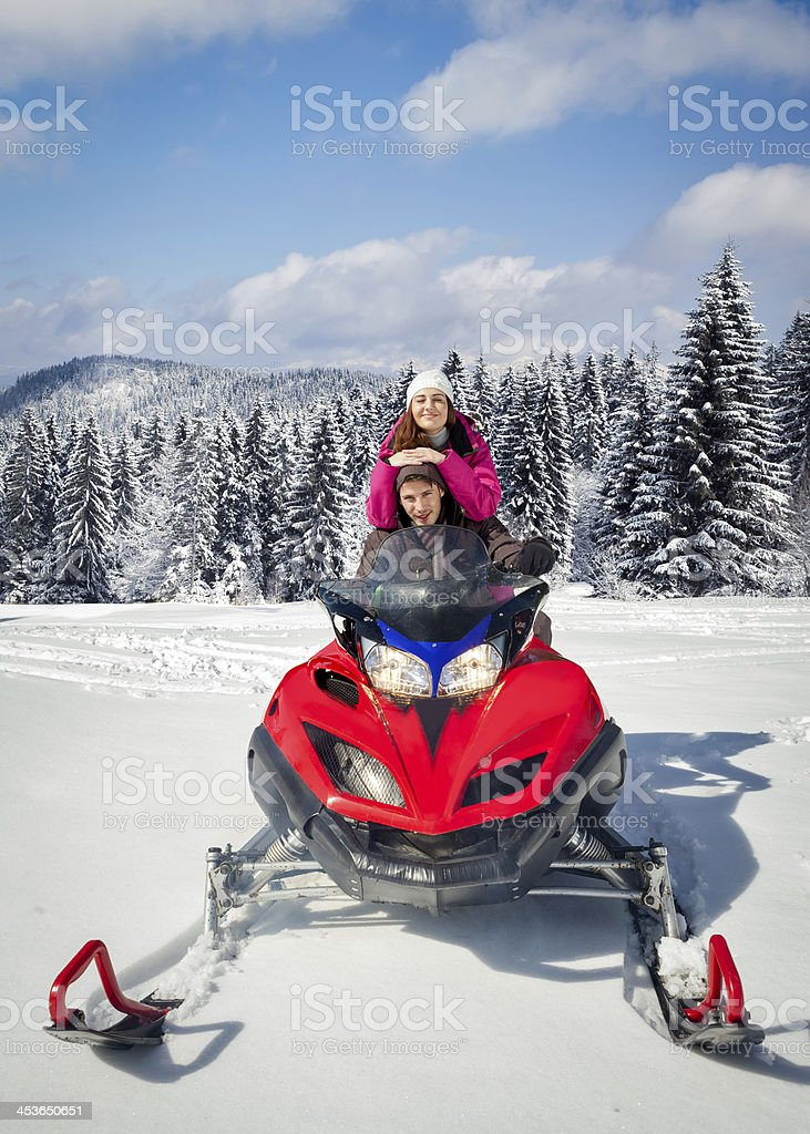 Couple driving snowmobile stock photo