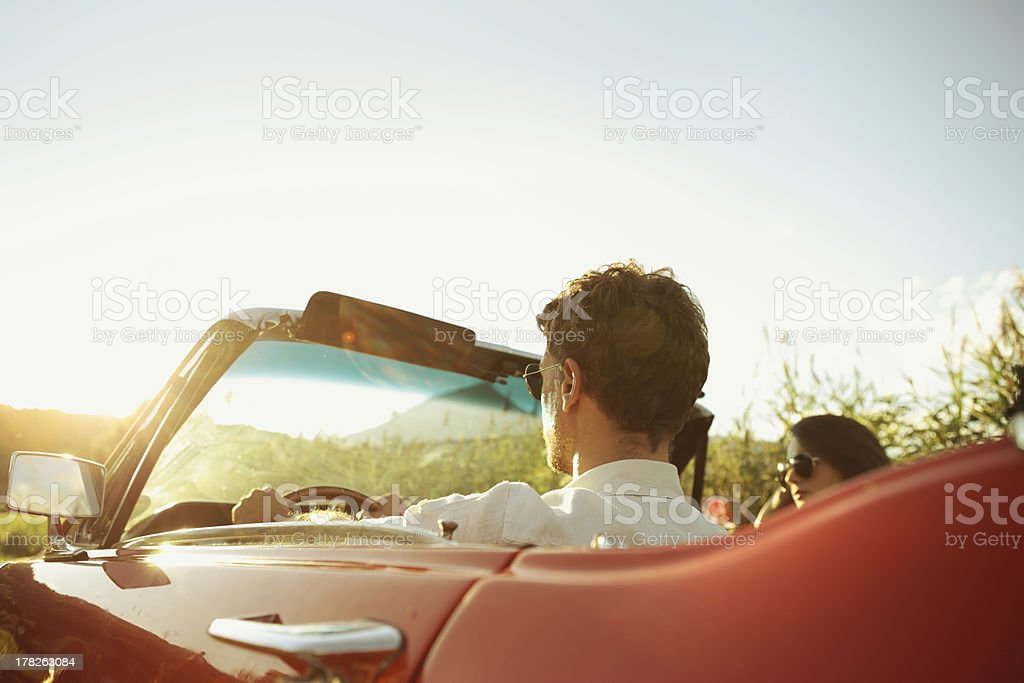 Couple driving through the country in red vintage car stock photo