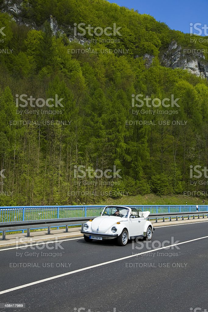 Couple Driving Vintage Volkswagen Beetle Convertible Down Valley in Spring stock photo