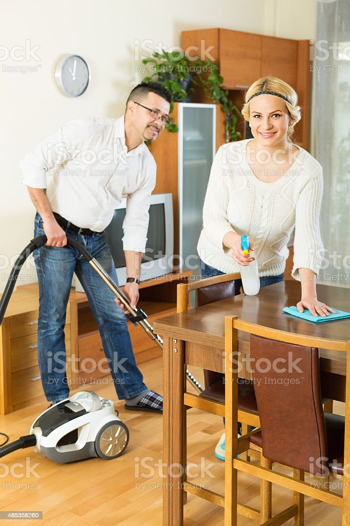 Couple dusting and hoovering stock photo