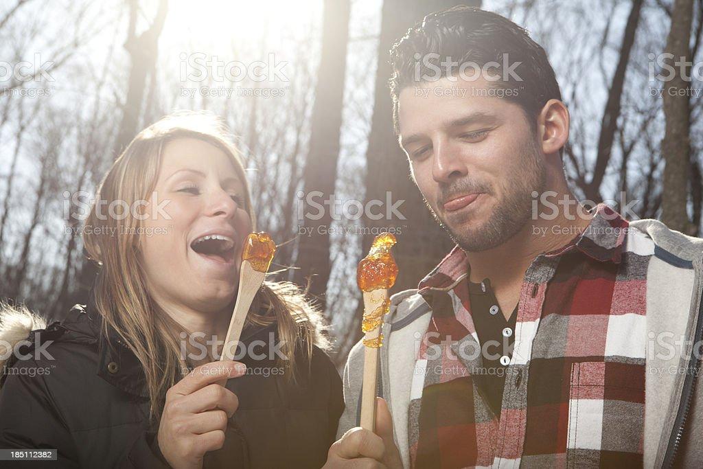 couple eat Maple taffy on a sunny day stock photo