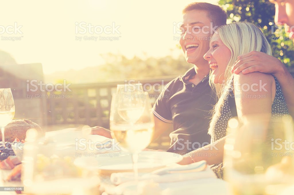 Couple eating at an outdoor restaurant with friends. stock photo