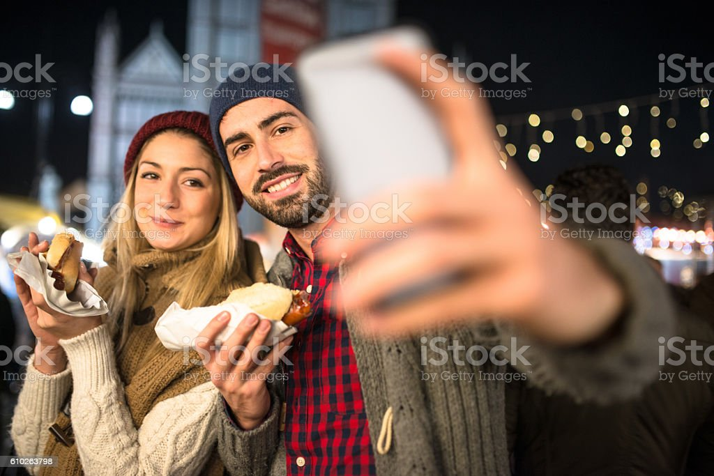 couple eating at the christmas market and take a selfie stock photo