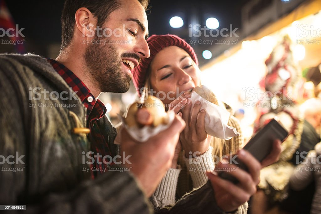 couple eating at the christmas market stock photo