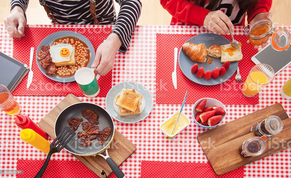 Couple eating breakfast, high angle view on table stock photo