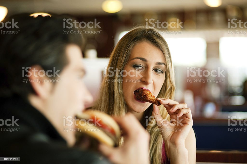 A couple eating fast food in a restaurant royalty-free stock photo