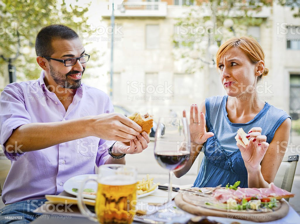 Couple Eating in Outdoors cafe: Woman refuses to eat burger stock photo