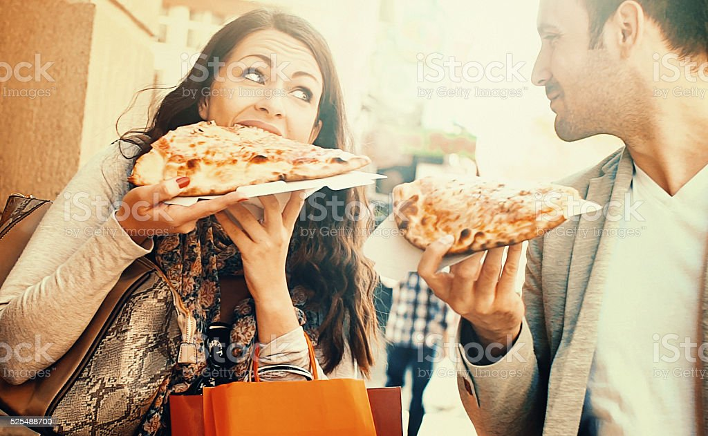 Couple eating pizza while walking. stock photo