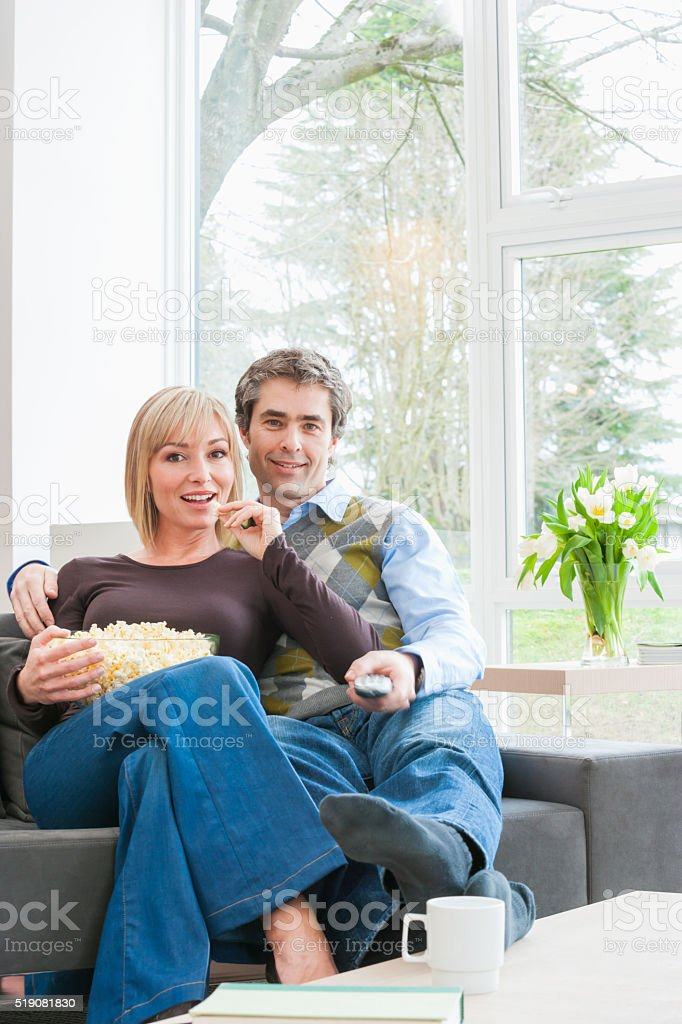 Couple eating popcorn and watching TV stock photo