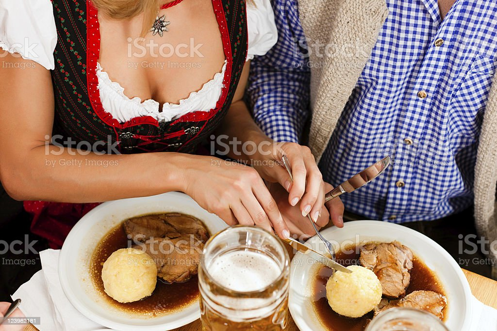 Couple eating roasted pork in a Bavarian restaurant royalty-free stock photo
