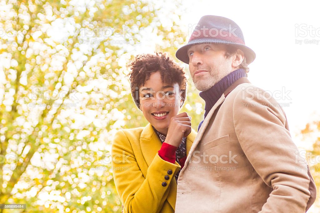 Couple embrace in the sun in an autumn day stock photo