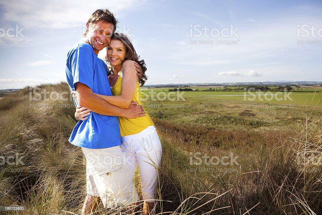 Couple embrace on sand dune royalty-free stock photo
